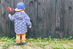 Barnanseende bredvid ett trästaket Outdoors Arkivbild