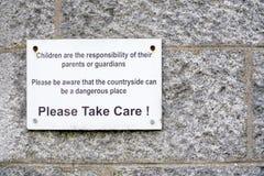 Barnansvar av föräldrar som bygden är det farliga stället, behar för att ta omsorgtecknet arkivfoto