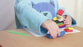 Barnarmar hugger diagram ut ur plasticine på tabellen stock video