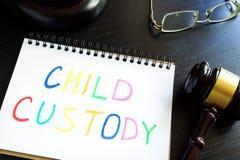 Barnarrest som är skriftlig i en anmärkning och en auktionsklubba Royaltyfri Fotografi