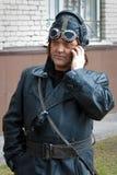 Barnaul, Rusia, el 9 de mayo de 2018: un hombre en un uniforme viejo del cuero de un piloto, aviador de los años 40 que habla en  Imagen de archivo