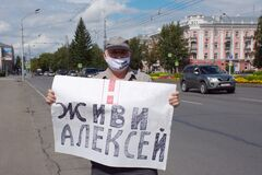 A man holds a placard in support of Alexey Navalny with the inscription ` Live, Alexey`