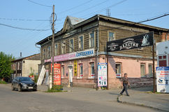 Barnaul, Russia, August, 17, 2016. Man walking near old wooden house on the street of Lev Tolstoy in Barnaul Royalty Free Stock Photo