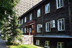 Barnaul, Russia, augusta, 17, 2016 Vecchia casa di legno nei precedenti in costruzione di alloggio moderno sulla via di Nikiti Fotografie Stock