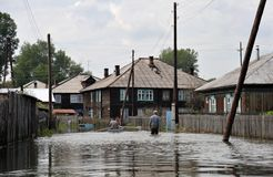 Locals move around the streets by boat. The Ob river, which came out of the banks, flooded the outskirts of the city. BARNAUL, RUSSIA - JUNE 26, 2010: Locals stock photos