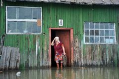 An unknown elderly woman in her home during a flood. The Ob river, which came out of the banks, flooded the outskirts of the city. Stock Images