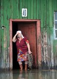 An unknown elderly woman in her home during a flood. The Ob river, which came out of the banks, flooded the outskirts of the city. Stock Image