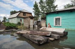 An unknown man on a flooded plot near his house. BARNAUL, RUSSIA - JUNE 26, 2010: An unknown man on a flooded plot near his house. The river Ob, which emerged royalty free stock images