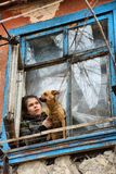 A girl with a dog in a poor quarter looking out the window of an old house royalty free stock image