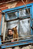 A girl with a dog in a poor quarter looking out the window of an old house stock images