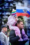 A man carries a child on his shoulders and the Russian flag royalty free stock photography