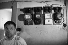 Barna A man in a poor quarter stands near electric meters stock images