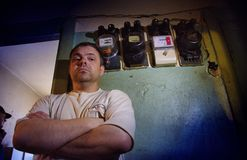 Barna A man in a poor quarter stands near electric meters stock image