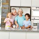 Barnbarn med morföräldrar i köket Royaltyfri Fotografi