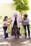 Barnbarn som hjälper farmodern till Carry Shopping Arkivfoton