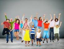 Barnberöm som hoppar extatiskt lyckabegrepp Arkivfoto
