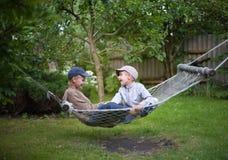 Barnbröder som talar trädgårds- utomhus- för land arkivbilder
