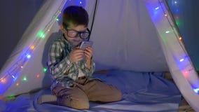 Barnbruk ringer i afton- eller nattsammanträde i en vigvam som dekoreras med en hemmastadd girland lager videofilmer