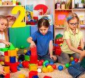 Barnbyggnadskvarter i dagis Gruppungar som spelar leksakgolvet arkivfoto