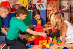 Barnbyggnadskvarter i dagis Gruppungar som spelar leksakgolvet royaltyfria bilder