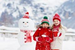 Barnbyggnadssnögubbe Ungar bygger snömannen arkivbild