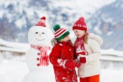 Barnbyggnadssnögubbe Ungar bygger snömannen Pojke och flicka som utomhus spelar på snöig vinterdag Utomhus- familjgyckel på jul royaltyfri foto