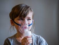 Barndanandeinandning med maskeringen på hans framsida Astmaproblembegrepp royaltyfri bild