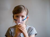 Barndanandeinandning med maskeringen på hans framsida Astmaproblembegrepp arkivbilder