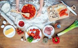 Barndanandepizza med pizzaingredienser, tomater, salami och champinjoner på trätabletopen Arkivfoton