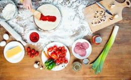Barndanandepizza med pizzaingredienser, tomater, salami och champinjoner på trätabletopen Arkivfoto