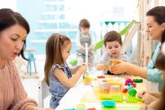 Barndeglek i daycaremitt Ungar gjuter från plasticine i dagis Små studenter knådar modellera lera med händer arkivfoto