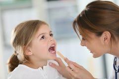 barndoktor som undersöker s-halsen arkivfoton