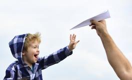 Barndom Barnson som spelar med pappersflygplanet Bekymmersl?st Frihet som drömmer - den glade pojken som spelar med det pappers-  arkivbilder
