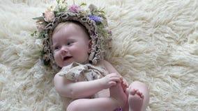 Barndom behandla som ett barn i beslag med blommalögner på filten och poserar på kameran på photoshoot stock video