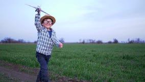 Barndom, grabben i exponeringsglas och hatten spelar med leksakflygplanet i ett fält lager videofilmer