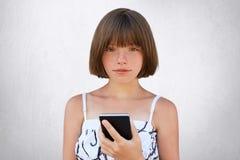 Barndom i digital ålder Gullig flicka med den korta stilfulla frisyren, mörka djupt liggande ögon och fräknar som bär den trevlig fotografering för bildbyråer