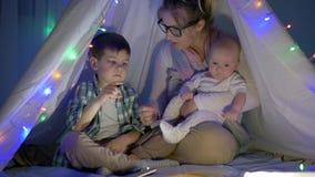 Barndom moder berättar berättelse till hennes barn i vigvammet med en dekorativ girland i afton stock video