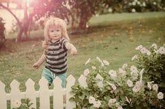 barndom och lycka utomhus- near vitt trästaket för lyckligt litet pojkebarn Royaltyfria Foton