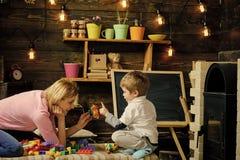 Barndombegrepp Familjlek med den hemmastadda konstruktörn Mamma- och barnlek med detaljer av konstruktörn, plast- tegelstenar Royaltyfri Fotografi