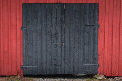 Barndoor in black with a red wall around. A black barn door with a red wall around Royalty Free Stock Photography