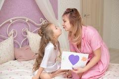 Barndottern gratulerar mamman och ger henne en vykort royaltyfri fotografi