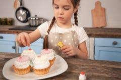 Barndottern i köket som dekorerar kakor göras hon, med hennes mamma r royaltyfri bild