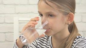 Barndricksvatten, törstig unge som studerar exponeringsglas av sötvatten, flicka i kök royaltyfria bilder