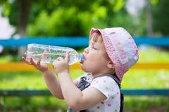 Barndrinkar från den plast- flaskan Arkivfoto