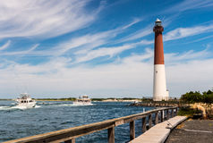 Barnegat Inlet and Lighthouse in Long Beach Island. Fishing boats heading out to sea, through Barnegat Inlet with Barnegat Lighthouse in background Royalty Free Stock Photos