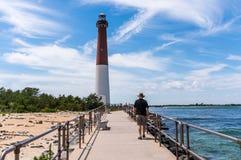 Barnegat Inlet and Lighthouse, Long Beach Island, NJ, USA. Man walking along Barnegat Inlet, toward Barnegat Lighthouse Royalty Free Stock Photos