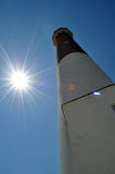 Barnegat Lighthouse. Low angle view of Barnegat or Old Barney Lighthouse with sun shining in sea blue sky background, Long Beach Island, New Jersey, America Stock Photography