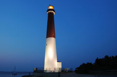 Barnegat Lighthouse At Dusk. Dusk picture of Barnegat Lighthouse in New Jersey. Light is on, sky is a dark blue, and spot lights enhance the house Stock Photography