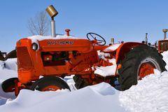 Old Allis Chalmers tractor buried in the snow royalty free stock photos