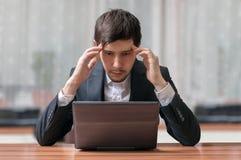 Barnet ämnar och den tänkande affärsmannen som arbetar med bärbara datorn royaltyfria bilder